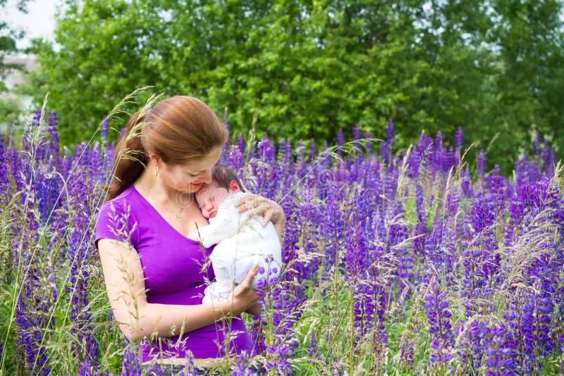 Generi la tenuta del suo neonato nel giacimento di fiore porpora fotografie stock
