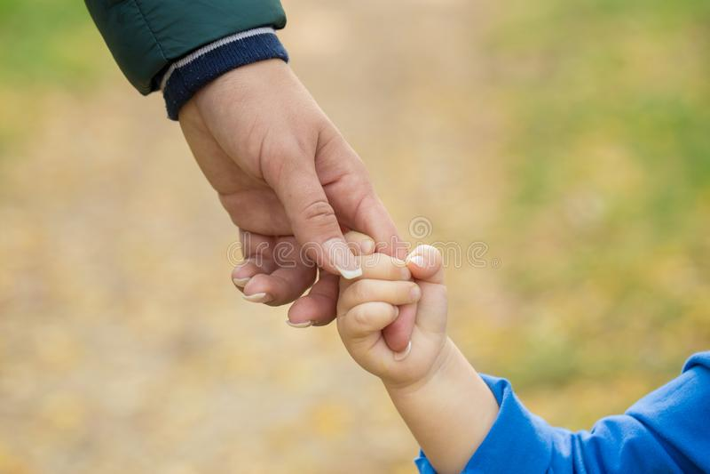 Generi la tenuta della mano di suo figlio nel giorno di estate all'aperto fotografia stock