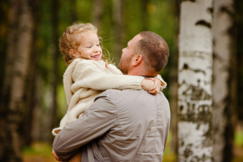 Generi la tenuta di sua figlia in un interruttore tricottato beige riccio affascinante fotografia stock libera da diritti