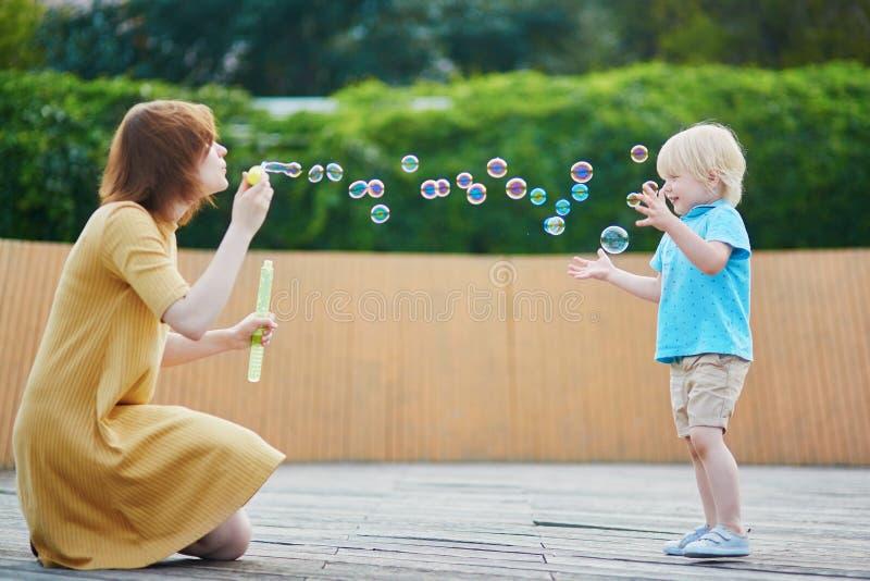 Generi le bolle di salto ed il gioco con suo figlio piccolo immagine stock libera da diritti