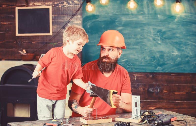 Generi, parent con la barba in casco protettivo che insegna al piccolo figlio a utilizzare gli strumenti differenti nell'officina immagine stock