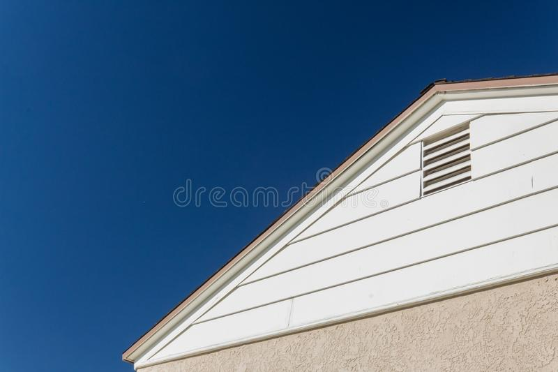 Generic house view of side and roof edge, stucco and vinyl with attic ventilation set against a deep blue sky. Copy space, horizontal aspect stock image