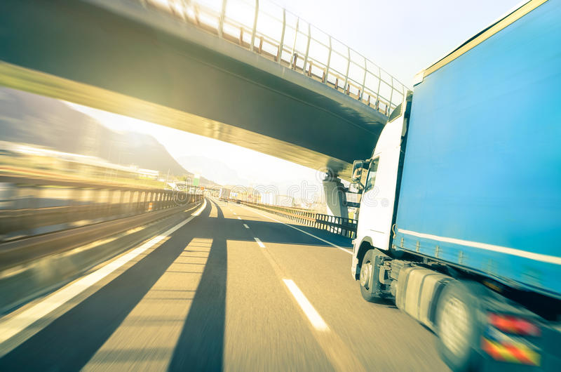 Generic semi truck speeding on highway - Logistic transport concept. Generic semi truck speeding on highway under overpass - Transport industry logistic concept royalty free stock photos