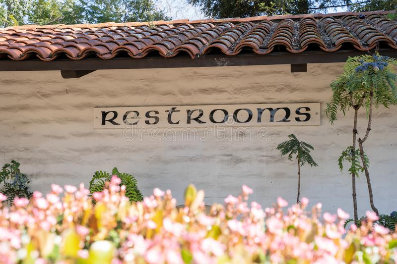 Generic sign for public restrooms - pretty pink flowers defocused in the foreground.  stock photo