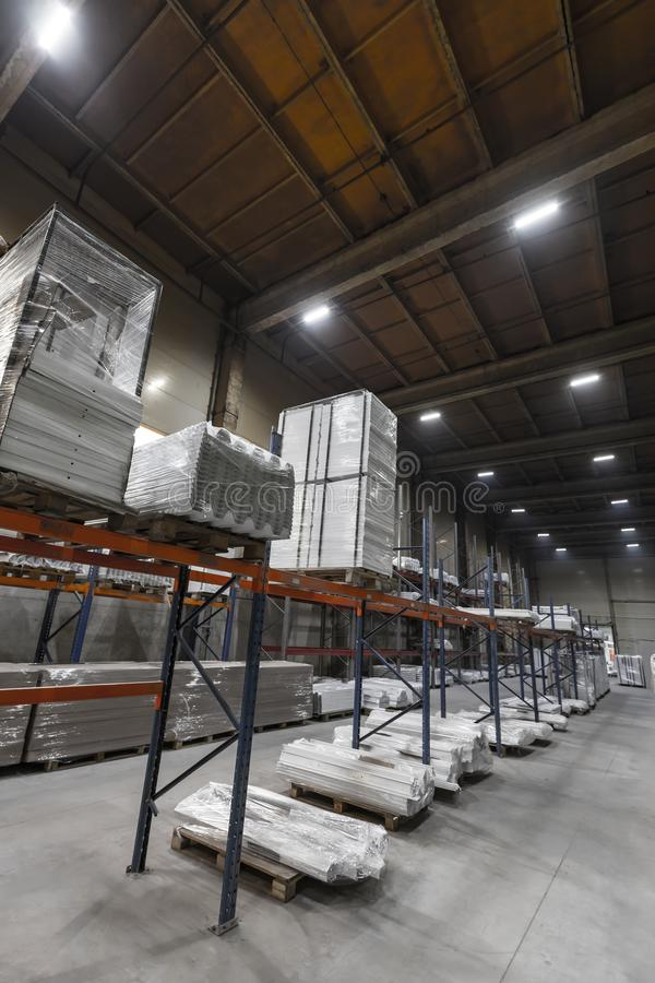 Generic warehouse industrial interior with palettes stacked on shelves. Wide angle view stock photography