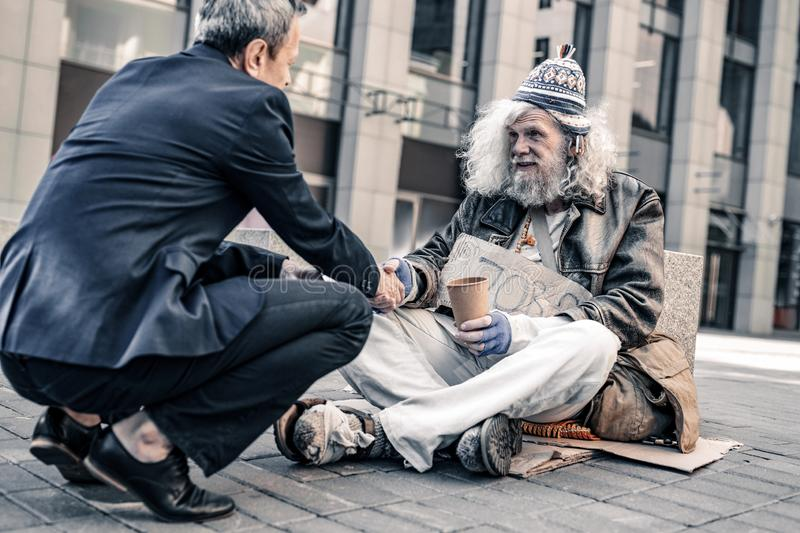Pleasant smiling rich man shaking hand of poor grey-haired homeless. Generous pedestrian . Pleasant smiling rich men shaking hand of poor grey-haired homeless stock images