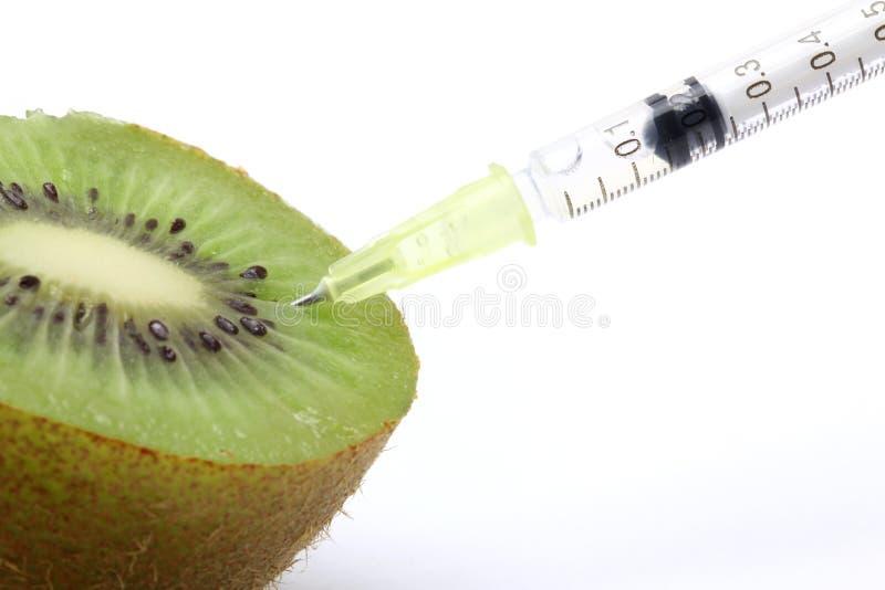Genetic food engineering. Concept with Kiwi & syringe royalty free stock photography