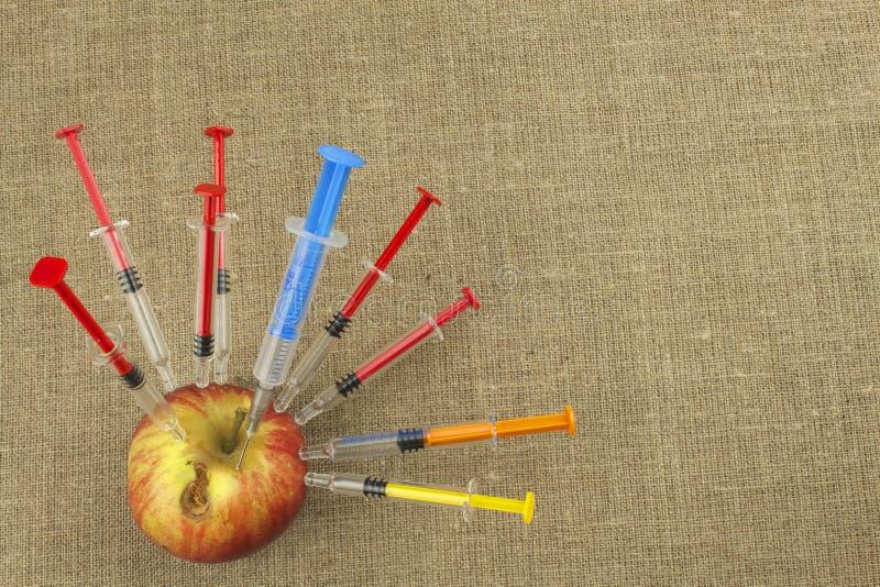 Genetiskt ändringsbegrepp Frukt och syginge Apple som mottar en injektion av någon vikt för snabbt mogna arkivbild