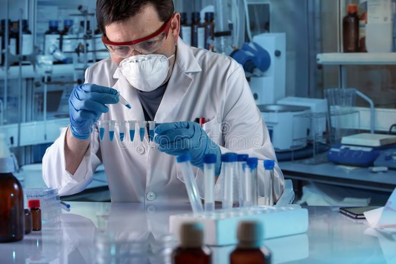 Genetista que sostiene los tubos de la polimerización en cadena para analítico genético en el laboratorio clínico fotos de archivo libres de regalías