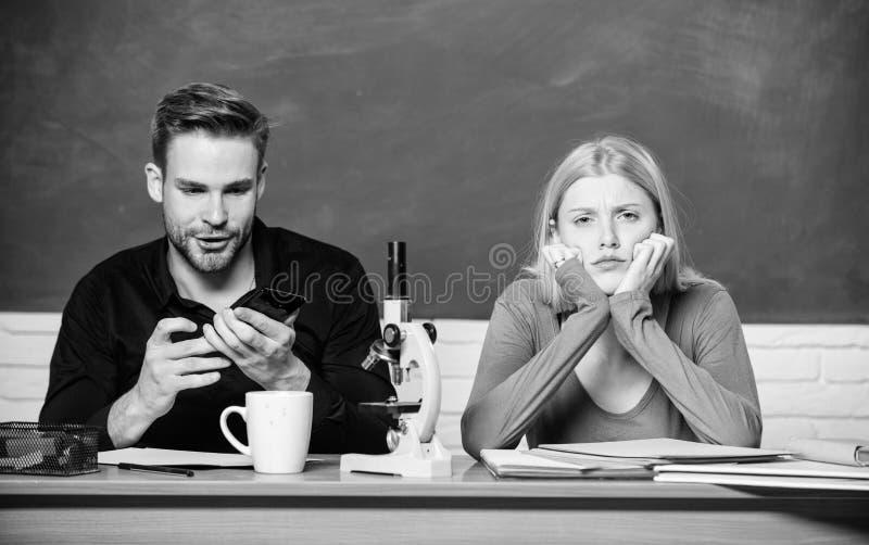 Genetyka i in?ynieria Trudny uniwersyteta temat eksperyment naukowy Facet i dziewczyna przy biurkiem z mikroskopem fotografia royalty free