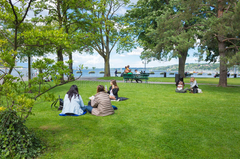 Geneva, Switzerland - June 17, 2016: The people sitting on the grass in a park the waterfront. Geneva, Switzerland - June 17, 2016: The people sitting on the stock photos