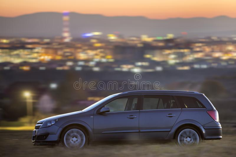 Geneva, Switzerland - October 9, 2018: Gray car moving at night in green meadows on background of lights of distant city buildings royalty free stock photography