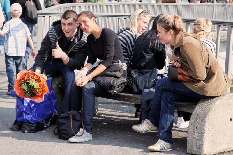 Genf, die Schweiz - Mai 2012: Die Gruppe von den jungen Leuten, die auf der Straßenbank vor dem Fluss sitzen Paare des Freunds, M stockfotografie