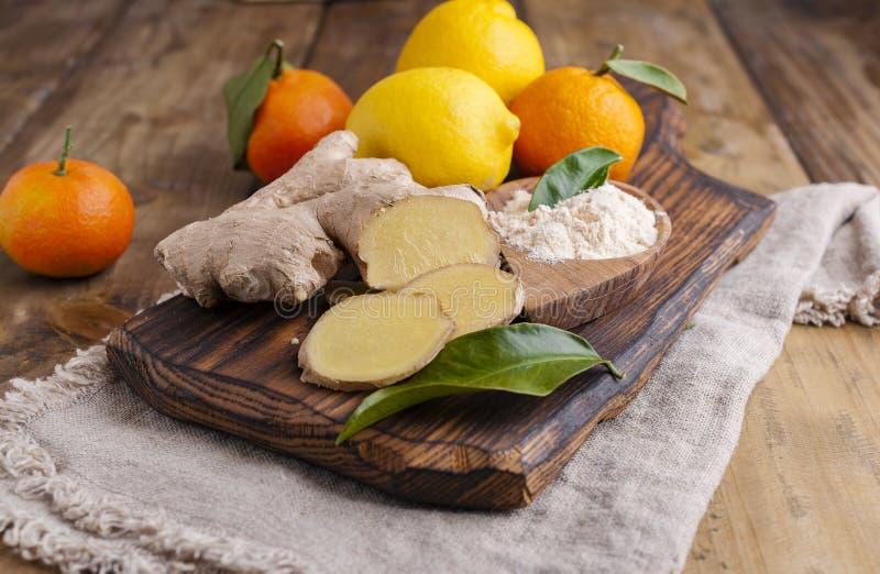 Gengibre e limão em um fundo de madeira, foto em um estilo rústico Ingredientes para a bebida do aquecimento e da saúde Medicina  fotografia de stock