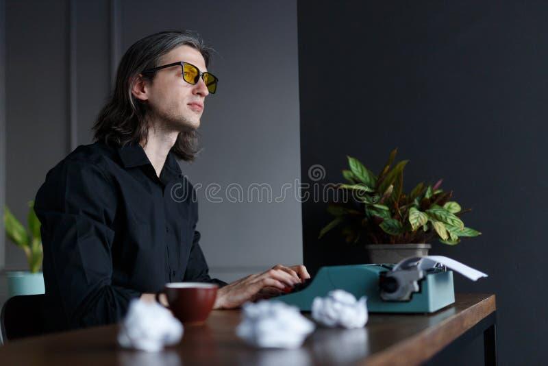 Genial ung författare som tänker om nya boken som arbetar på en gammal tappningskrivmaskin som i regeringsställning placeras på e royaltyfri fotografi