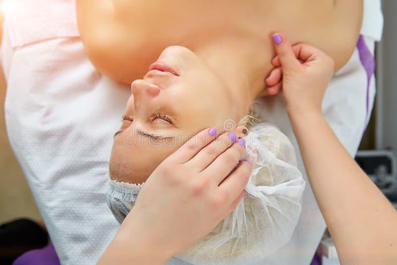 Genießen der jungen Frau der Gesichtsmassage im Badekurortsalon lizenzfreies stockbild