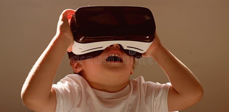 Genießen der neuen Technologie Kleines Kind in VR-Kopfhörer Drahtlose VR Gläser der kleinen Kinderabnutzung Unter Verwendung der  stockfotos