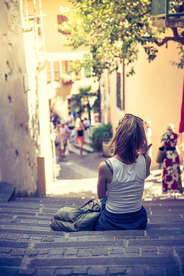 Genießen der Sommerferien: Junges Mädchen sitzt auf der steinigen Treppe und dem Stillstehen lizenzfreie stockfotos