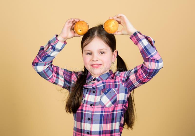 Genießen ihres Lieblingsmuffinaromas Glückliche Holdingfrühstücksmuffins des kleinen Mädchens am Kopf Kleines Kindergl stockfotos