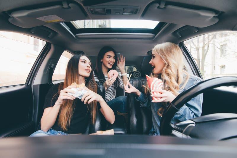 Genießen ihres Mittagessens im Auto Vier schöne junge nette einander mit Lächeln betrachtende und essende Frauen nehmen Lebensmit stockfotos