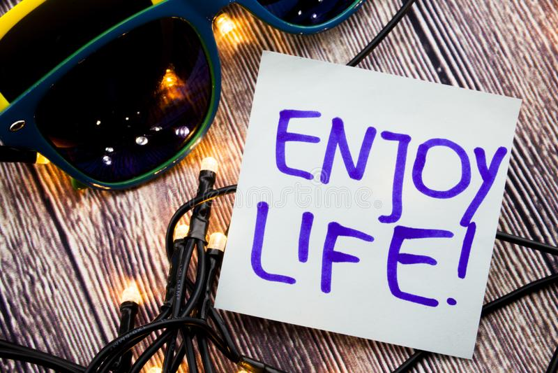 Genießen Sie handgeschriebene Motivmitteilung des Lebens auf einem Papier mit blauer Farbe auf hölzernem Hintergrund mit den Lich lizenzfreie stockfotos