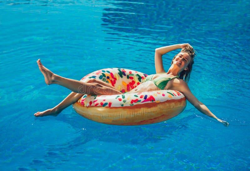 Genießen von Sonnenbräune Frau im Bikini auf der aufblasbaren Matratze im Swimmingpool stockbilder