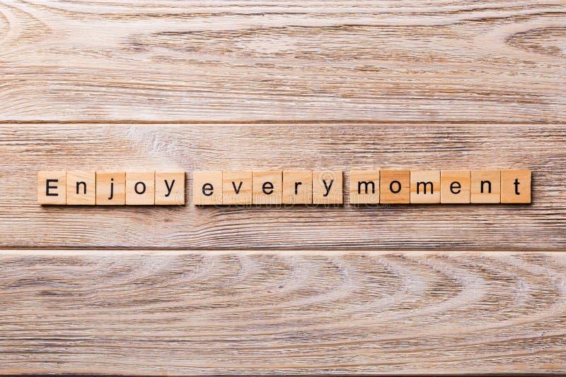 Genießen Sie jedes Momentwort, das auf hölzernen Block geschrieben wird Genießen Sie jeden Momenttext auf Holztisch für Ihr Desin lizenzfreie stockbilder