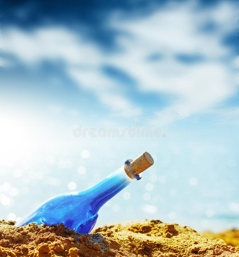 Genie. Blue glass bottle in sand and airy clouds like genie