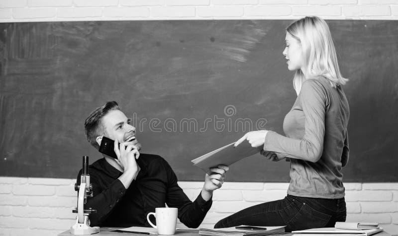 Genie?en des Studentenlebens Hochschul- oder Studenten Ordnende Papiere des h?bschen Lehrers und des h?bschen Schulleiters paare stockfoto