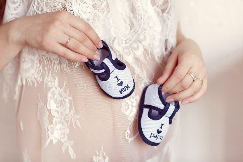 Genie?en des zuk?nftigen Lebens Schwangere Frau, die kleine Babybeuten an ihrem Bauch, Nahaufnahme hält stockfoto