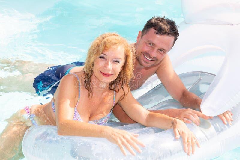 Geniet het levensstijl hogere paar die op een boei in de pool liggen van vakantie en rust stock afbeeldingen
