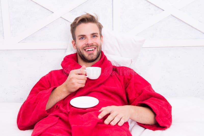 Geniet ochtend van koffie Gelukkige ochtend Knappe de ochtendkoffie van de mensendrank gelukkige gebaarde mens in bed Goede stemm royalty-vrije stock afbeelding