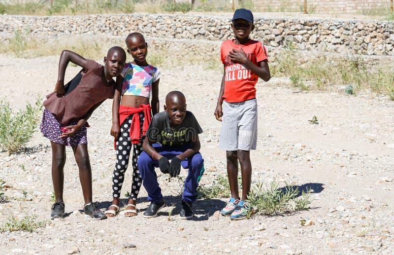 Geniet van de Afrikaanse jeugd vier twee meisjes en twee jongens stellend voor foto stock afbeelding