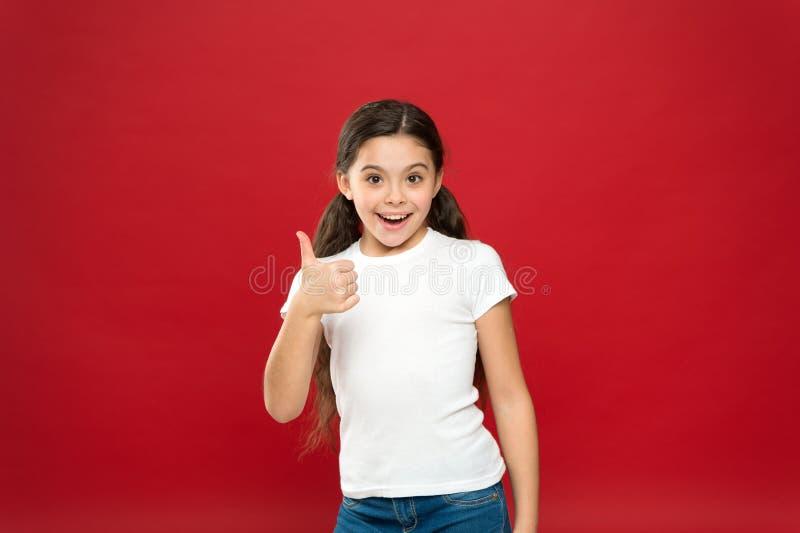 Geniet van Elk Ogenblik Gelukkig kindmeisje met lang haar op rode achtergrond Geluk en vreugde Positieve emoties Kinderverzorging stock fotografie