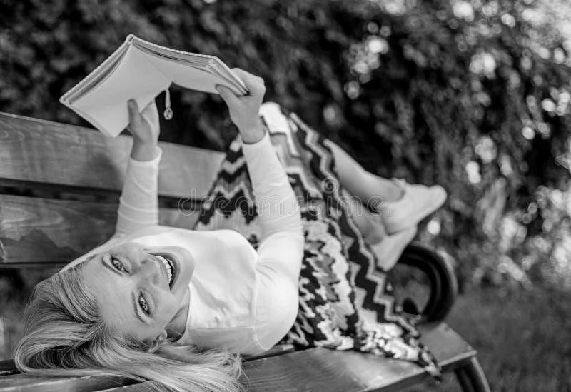 Geniet van het dame gelukkige gezicht lezend Tijd voor zelfverbetering Het meisje legt bankpark het ontspannen met boek, groene a royalty-vrije stock afbeelding