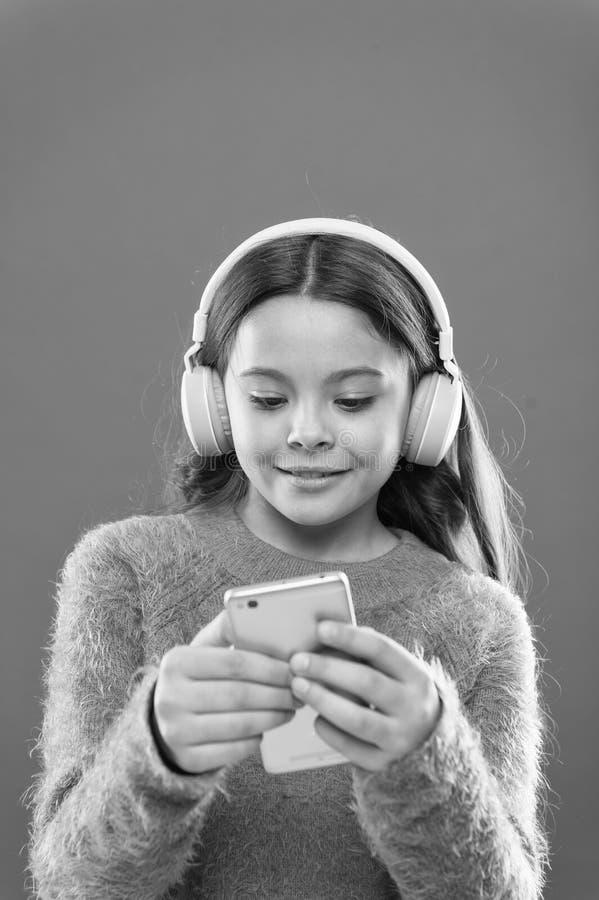 Geniet van perfect geluid Beste muziek apps kostenloos Het meisjeskind luistert muziek moderne hoofdtelefoons en smartphone Let o royalty-vrije stock afbeeldingen