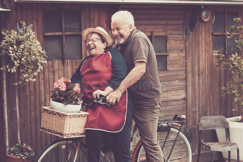 Genieten de Kaukasische mensen van Nice van vrije tijd openlucht allebei op één enkele fiets die als gek lauhing samen grappige o royalty-vrije stock afbeeldingen