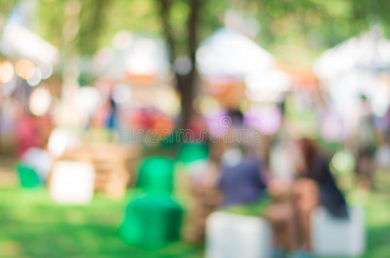 Genieten van de samenvatting vage mensen etend bij de gebeurtenis van het voedselfestival in het stedelijke park royalty-vrije stock foto