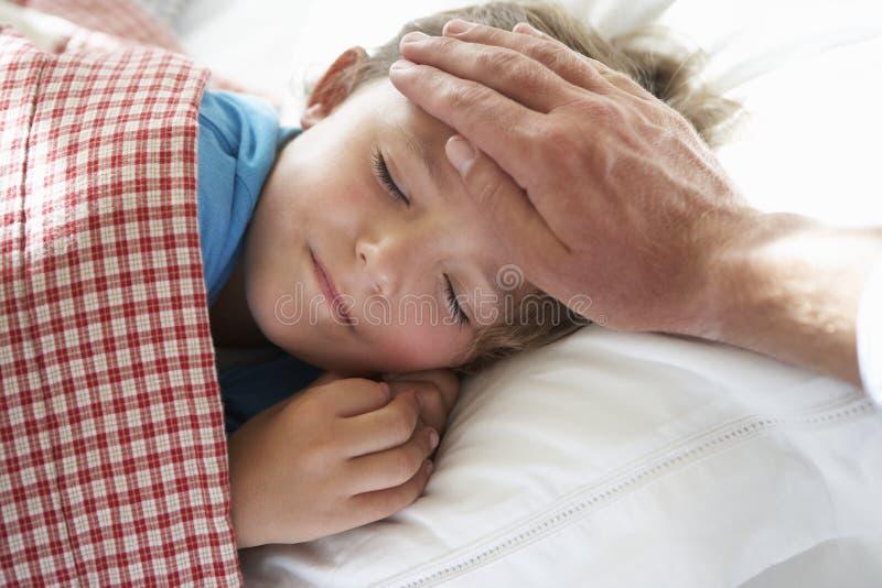 Genitore che prende temperatura di giovane ragazzo addormentata a letto fotografie stock libere da diritti