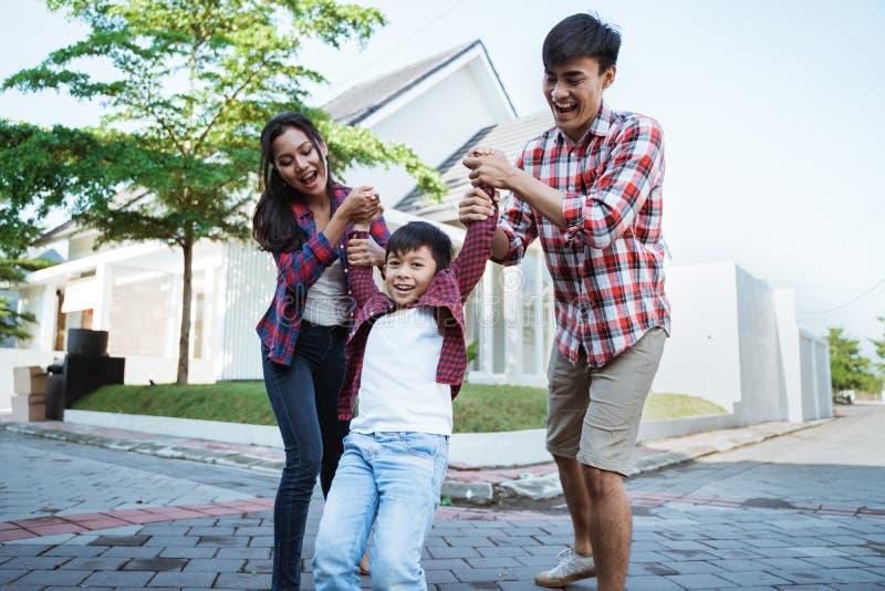 Genitore con il bambino che gode del gioco insieme davanti alla loro casa nuova fotografie stock