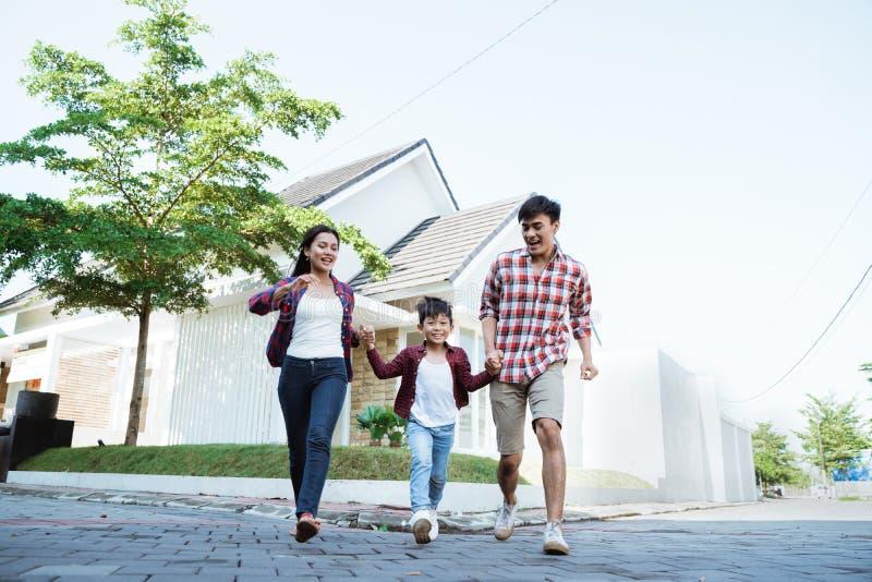 Genitore con il bambino che gode del gioco insieme davanti alla loro casa nuova fotografia stock libera da diritti