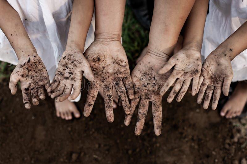 Genitore e bambini della famiglia che mostrano le mani sporche dopo la piantatura dell'albero insieme immagini stock