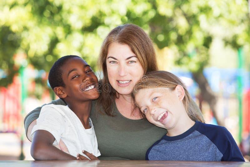 Genitore non coniugato allegro con i figli alla tavola del parco fotografia stock libera da diritti