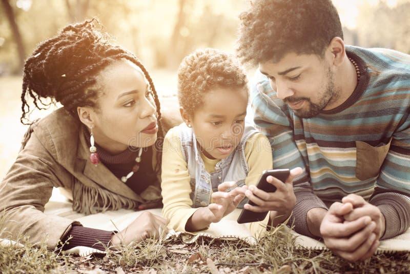 Genitori afroamericani giovani in parco con la figlia che usando mobil immagine stock libera da diritti
