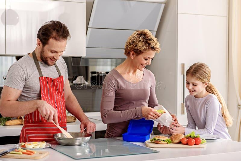 Genitori allegri che preparano alimento per la figlia immagine stock