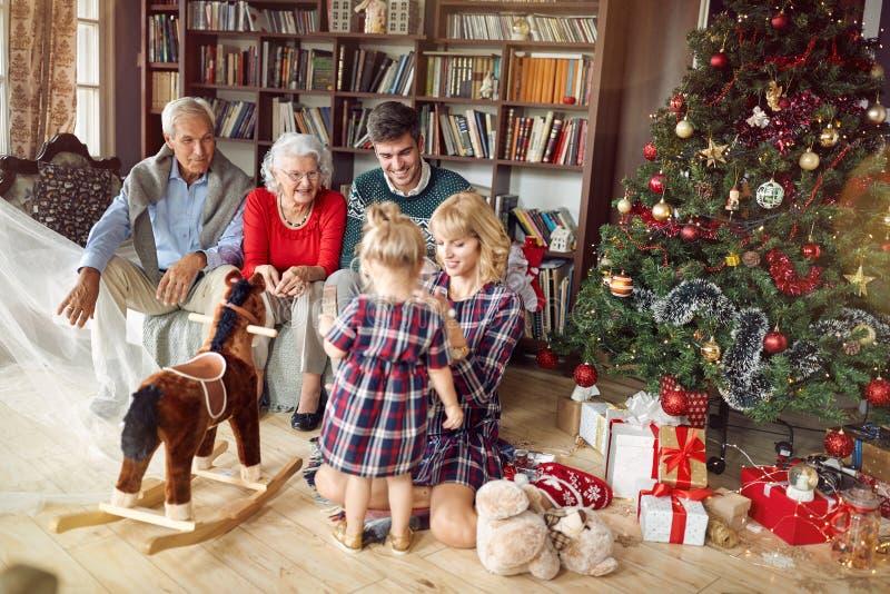 Genitori allegri con i nonni e la bambina insieme per il Natale immagini stock libere da diritti