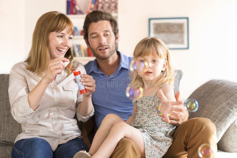 Genitori allegri e bolle di salto della figlia nella casa moderna bianca fotografia stock libera da diritti