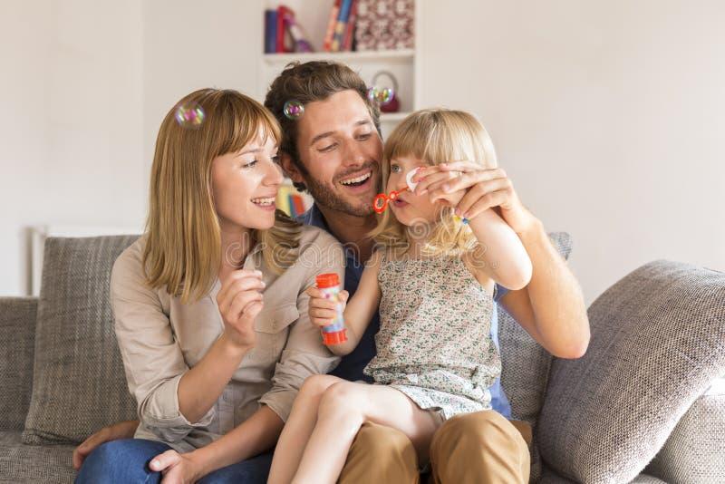 Genitori allegri e bolle di salto della figlia in noioso moderno bianco fotografie stock libere da diritti