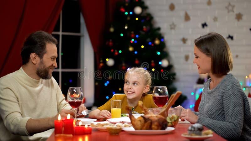 Genitori allegri e figlia che mangiano insieme insalata fresca la vigilia di natale, festa fotografie stock