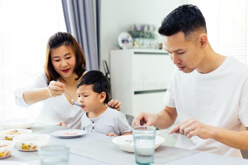 Genitori asiatici che alimentano insieme il loro bambino e l'intera famiglia che ha pasto a casa fotografia stock